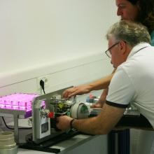 """Herr Professor Ewald verbindet das """"Liquid Exchange Device"""", unter der Anweisung von Frau Dr. Serena Bertone, mit dem Photobioreaktor."""
